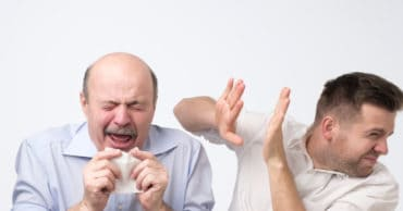 Sick bald caucasian man holding napkin or tissue, trying to cover mouth while sneezing with closed eyes. His coworker try to hide from microbes. Poor guy has terrible grippe